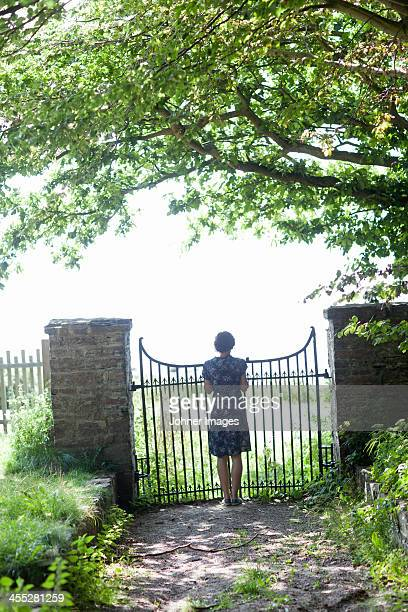 Woman standing in front of gate, rear view