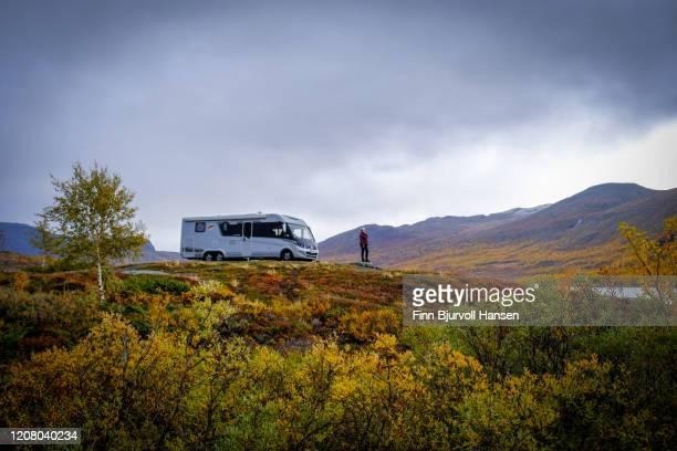 woman standing in front of her motorhome in the norwegian mountains - finn bjurvoll stock-fotos und bilder