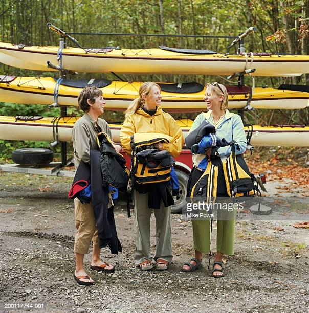 woman standing in front of kayaks, holding lifejackets, laughing - sea kayaking stock pictures, royalty-free photos & images