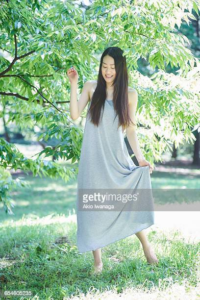 woman standing in front of leaves - akio iwanaga ストックフォトと画像