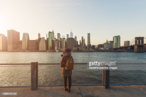 woman standing in front of manhattan, new york - amérique du nord photos et images de collection