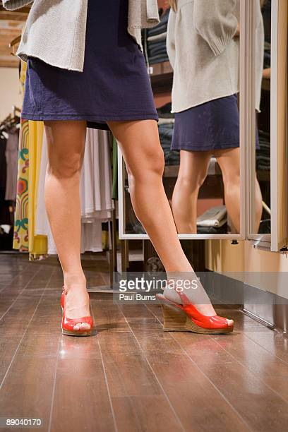 Woman Standing in Front of Mirror in Retail Store