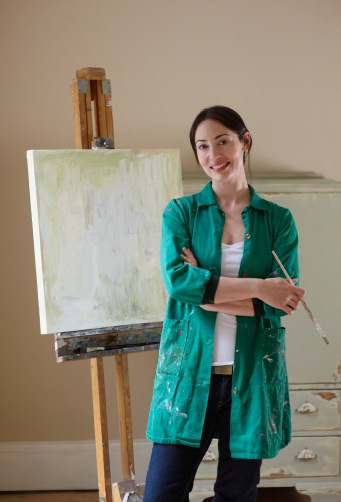 Woman standing in front of painted canvas. - gettyimageskorea