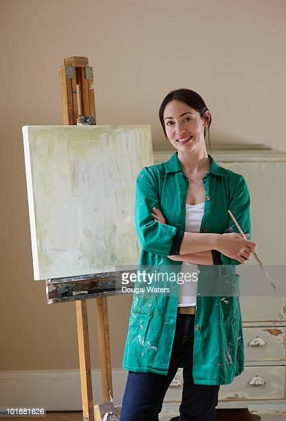 Woman standing in front of painted canvas.