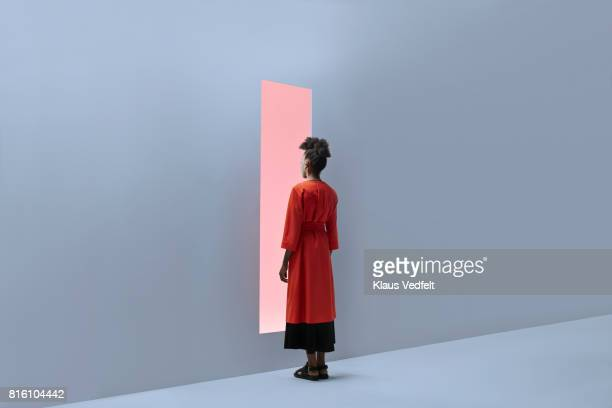 woman standing in front of rectangular opening in coloured wall - pink coat stock pictures, royalty-free photos & images