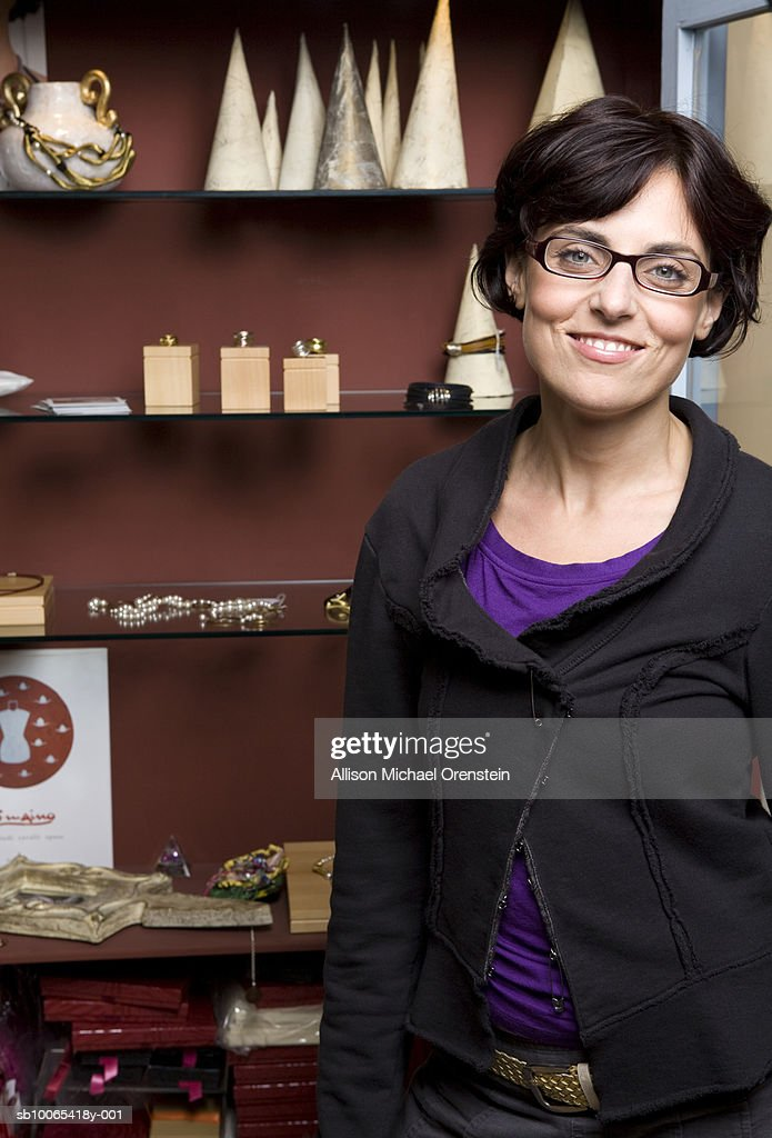 Woman standing in front of shelf with jewellery, portrait : Foto stock