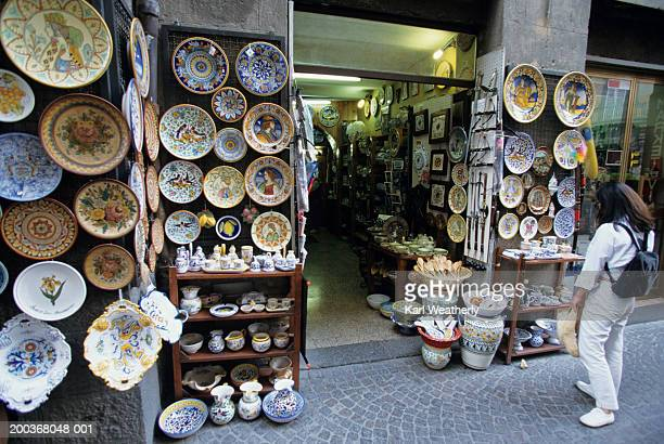 Woman standing in front of shop, looking at pottery, Orvieto, Italy