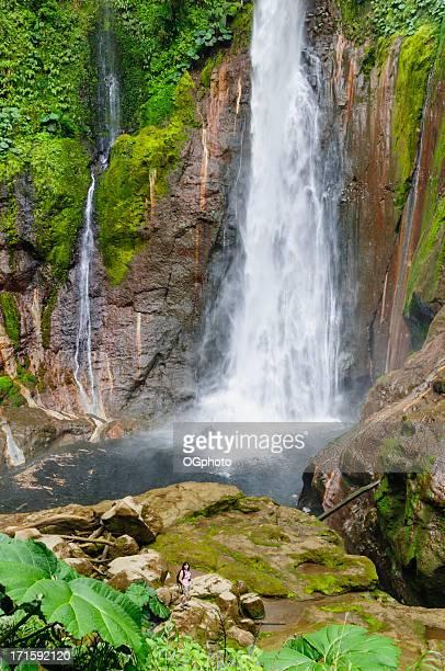 woman standing in front of towering tropical waterfall - ogphoto stockfoto's en -beelden