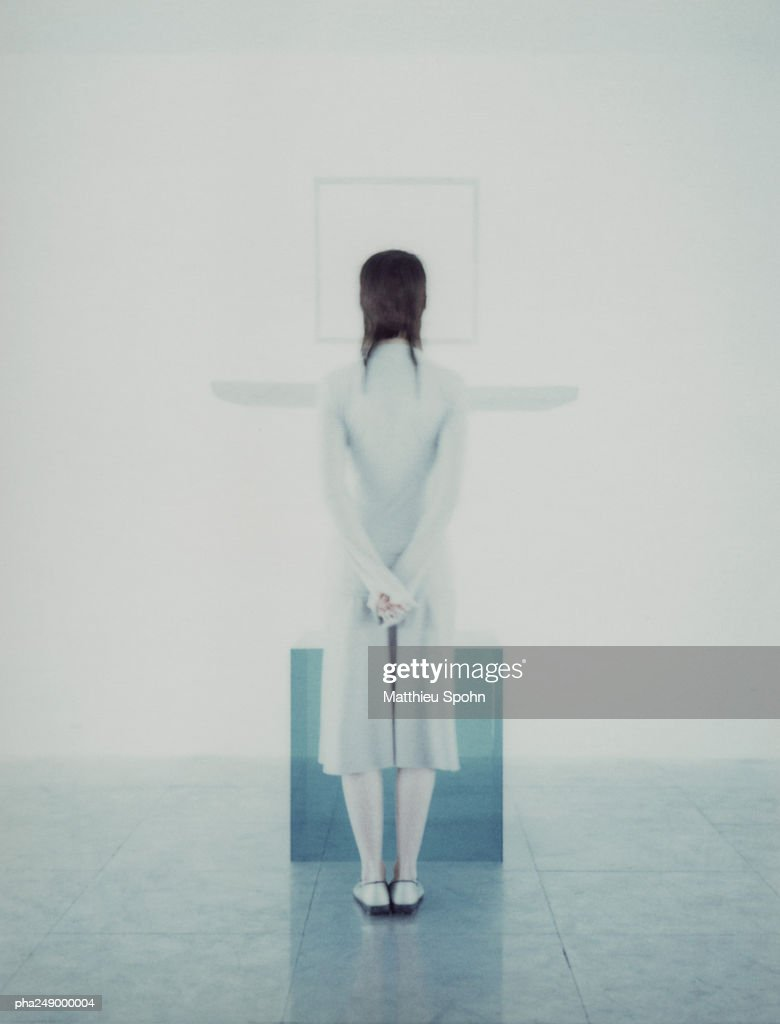 Woman standing in front of translucent cube, rear view : Stockfoto