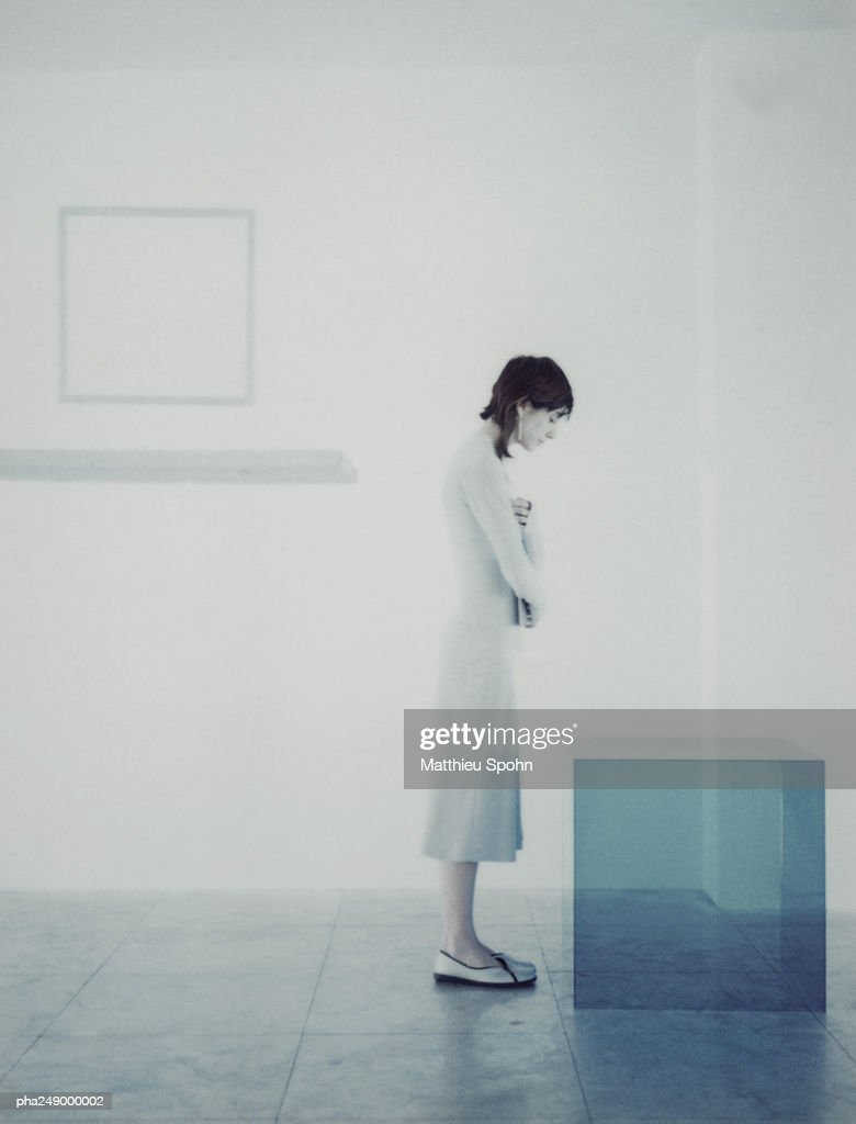 Woman standing in front of translucent cube, side view : Stockfoto