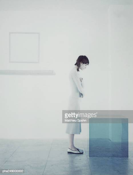 Woman standing in front of translucent cube, side view
