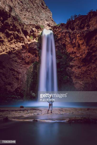 woman standing in front of waterfall - grand canyon village stock photos and pictures