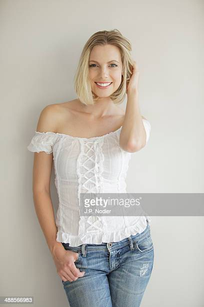 woman standing in front of white wall, smiling - mid length hair stock pictures, royalty-free photos & images
