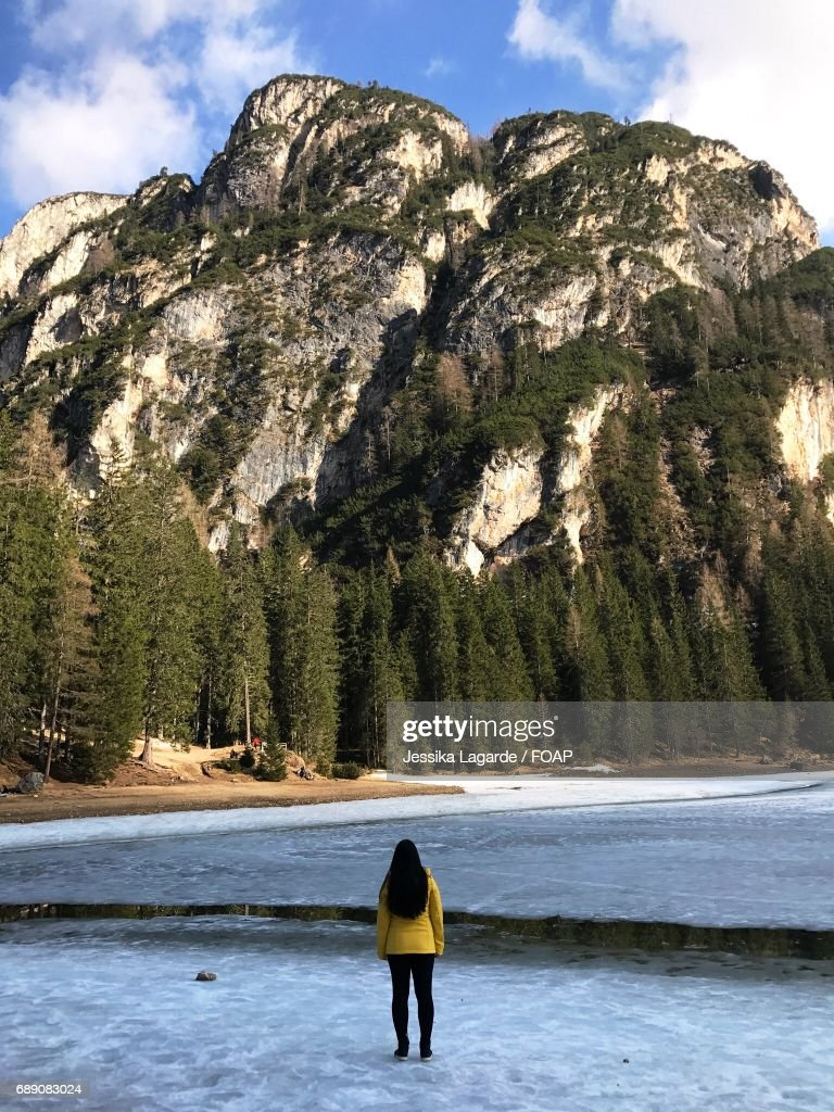Woman standing in frozen lake, Italy - Lago di Braies : Stock Photo