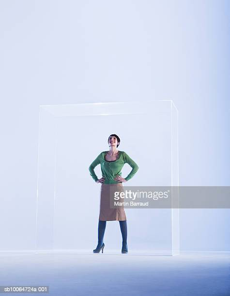 Woman standing in glass cabinet with hand on hip