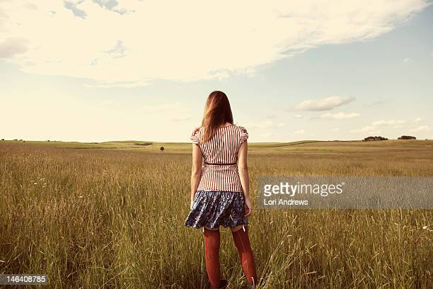 woman standing in golden prairie field - short skirts and stockings stock photos and pictures