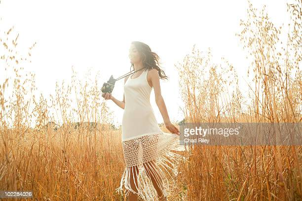 Woman standing in grass with camera