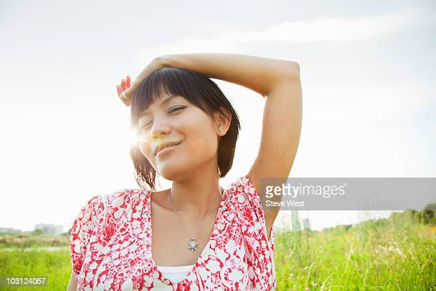 woman standing in grassy meadow with hand on head - short sleeved stock pictures, royalty-free photos & images