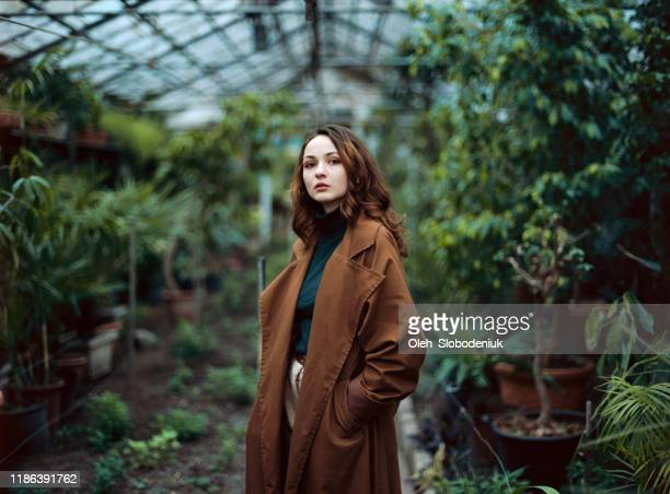 woman standing in greenhouse - coat stock pictures, royalty-free photos & images