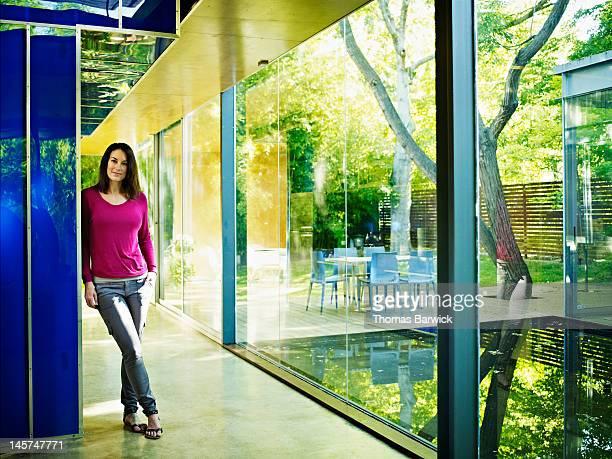 Woman standing in hallway of glass walled home