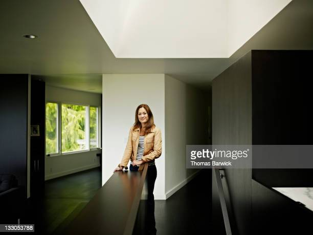 Woman standing in home under skylight