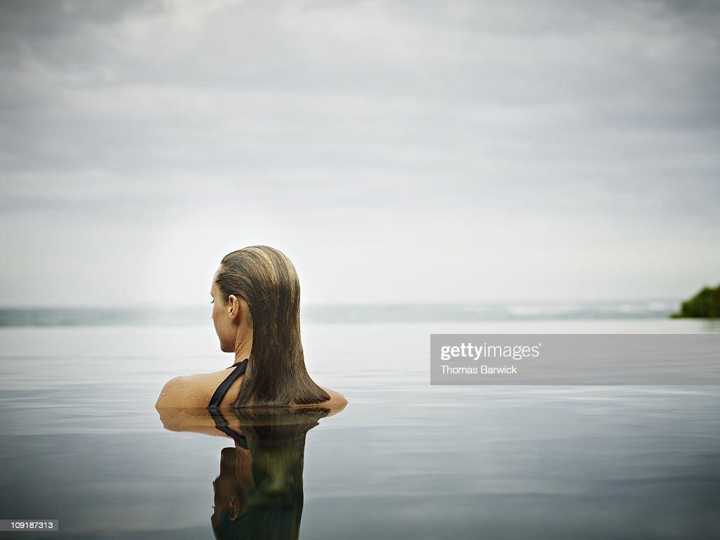 Woman standing in infinity pool overlooking ocean : Stock Photo