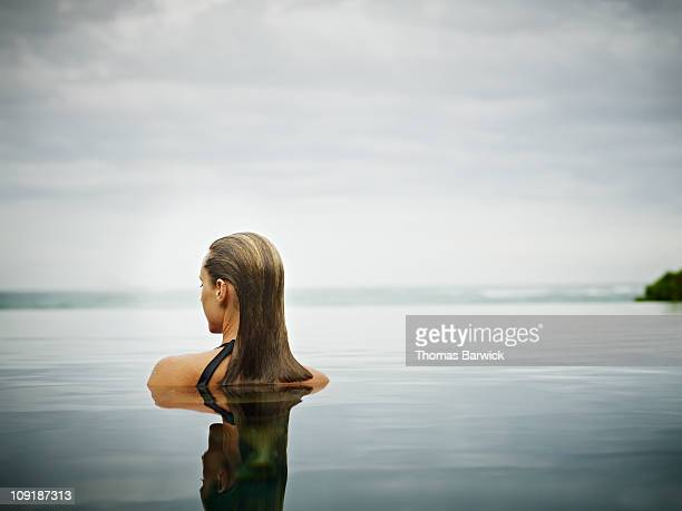woman standing in infinity pool overlooking ocean - zen like stock pictures, royalty-free photos & images