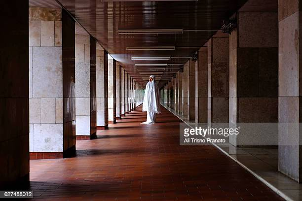 woman standing in istiqlal mosque. jakarta, indonesia. - masjid istiqlal stock pictures, royalty-free photos & images