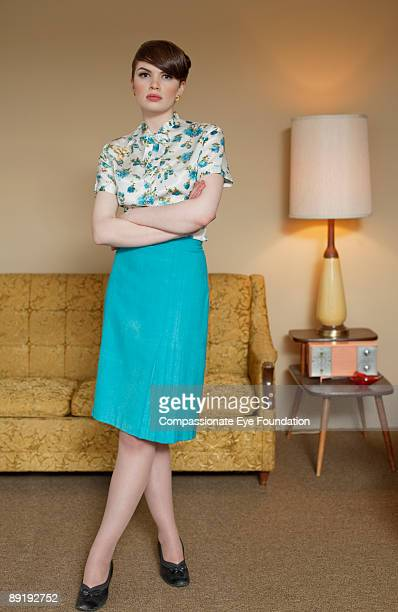 woman standing in living room with arms crossed
