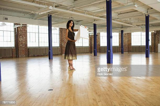 woman standing in loft holding building plans - dessin erotique photos et images de collection