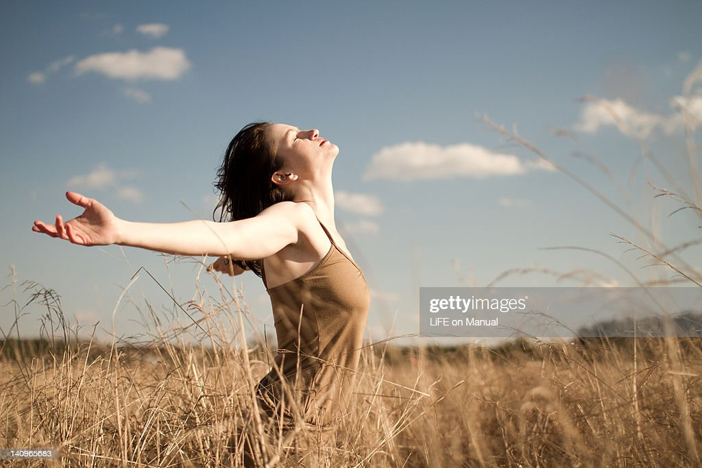 Woman standing in long grass : Stock Photo