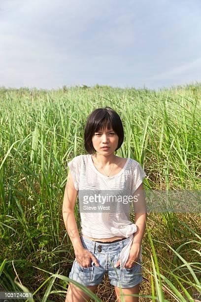 Woman standing in long green grass near riverside
