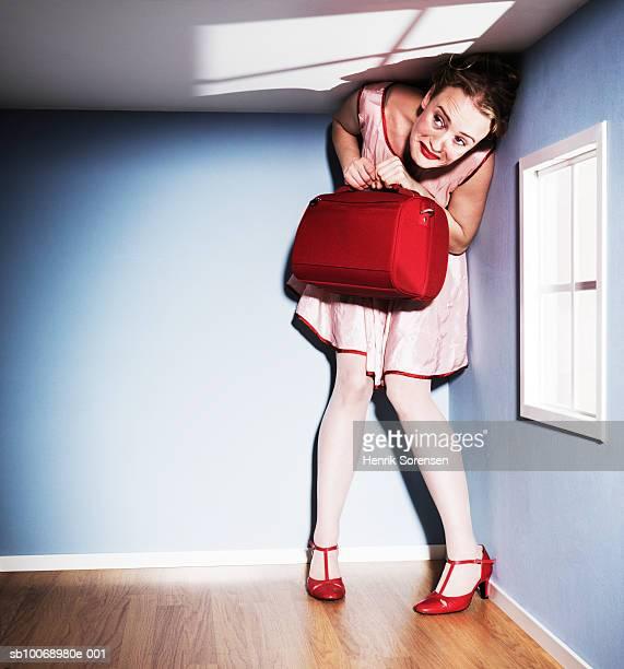 woman standing in low ceiling room, holding briefcase - surdimensionné photos et images de collection