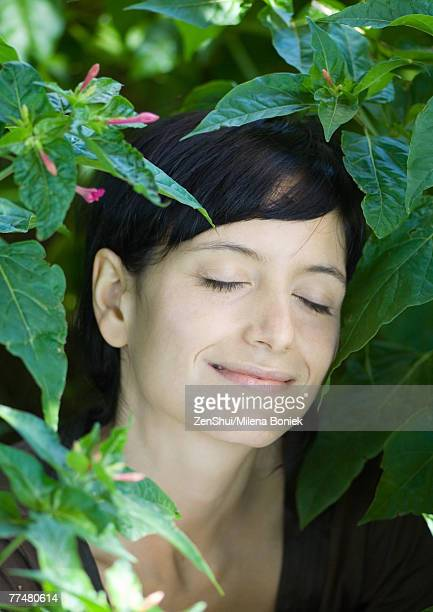 Woman standing in lush foliage, eyes closed, smiling