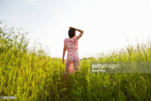 Woman standing in meadow looking into distance