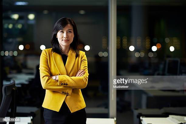 woman standing in office at night - zakenvrouw stockfoto's en -beelden