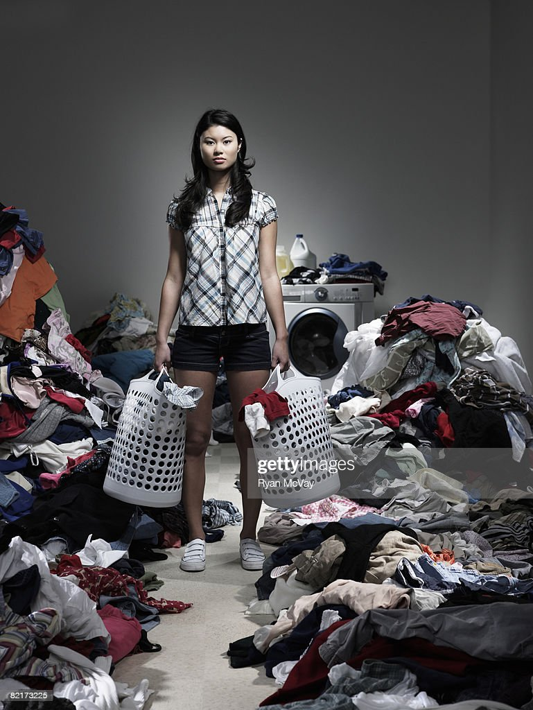 Woman standing in overflowing laundry room : Stock Photo