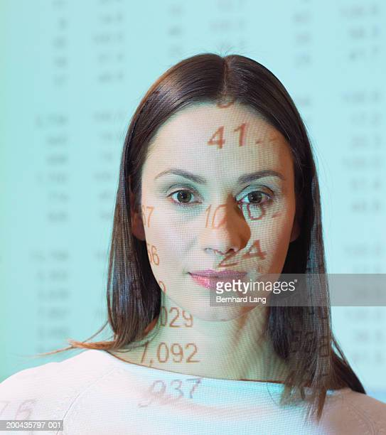Woman standing in overhead projector light, portrait