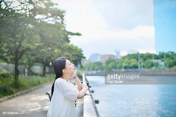 woman standing in park along the river - blouse ストックフォトと画像