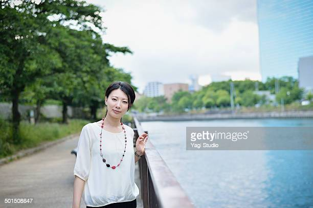 Woman standing in park along the river