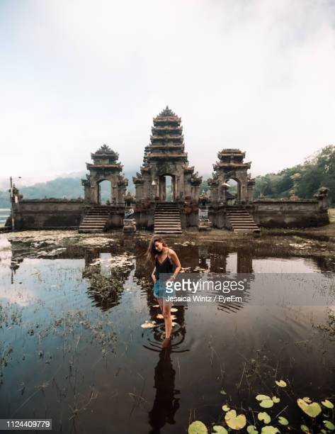woman standing in pond against temple - stagno acqua stagnante foto e immagini stock