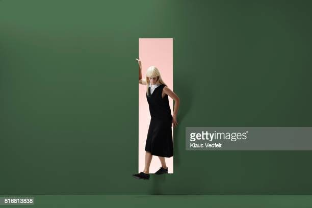 woman standing in rectangular opening of coloured wall - grüner hintergrund stock-fotos und bilder