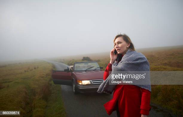 woman standing in road and making phone call with car in background. - vehicle breakdown stock pictures, royalty-free photos & images