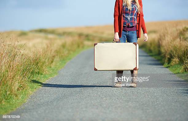 Woman standing in road with suitcase.