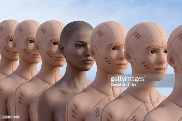 woman standing in row of robots - android stock pictures, royalty-free photos & images