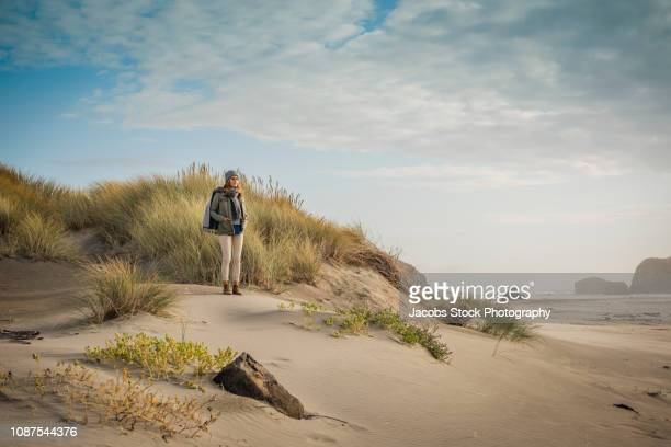 woman standing in sand dunes - dunes arena stock pictures, royalty-free photos & images