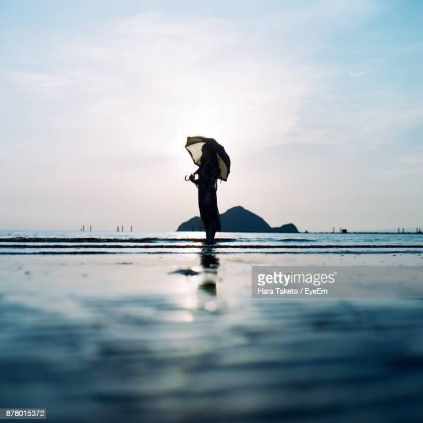 Woman Standing In Sea Against Sky On Sunny Day