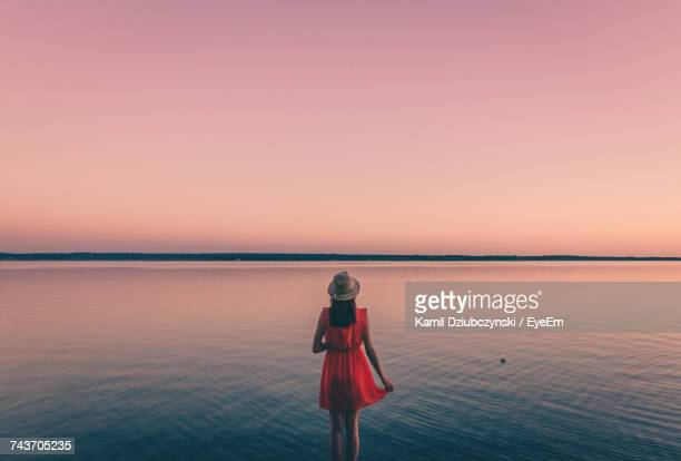Woman Standing In Sea Against Sky