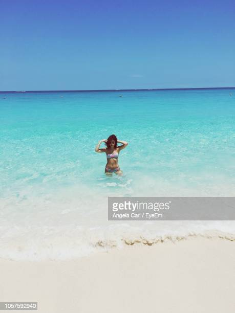 woman standing in sea at beach - cari stock pictures, royalty-free photos & images