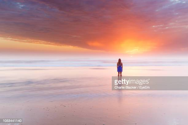 woman standing in sea during sunset - mid distance stock pictures, royalty-free photos & images